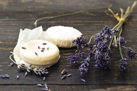 lavandula angustifolia: Closeup of natural herbal soap with lavender flower on a dark wooden background