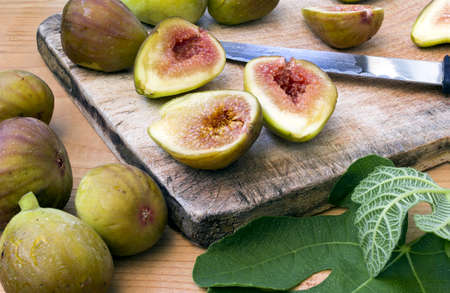 Fresh and healthy organic figs on a wooden board slashed in half Stock Photo