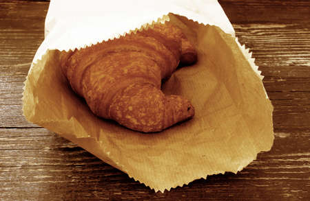 fancy bag: Fresh croissants in a paper bag on a wooden background.Toning effect