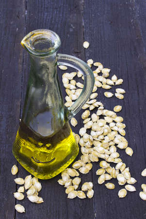 Pumpkin seed oil in bottle with seeds on wooden background