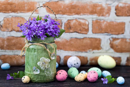 Easter holiday decoration with violet flowers and painted eggs Stock Photo