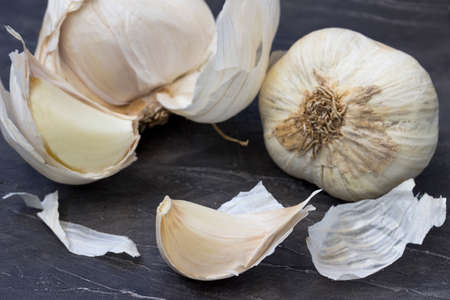Garlic bulbs with garlic cloves on the wooden background