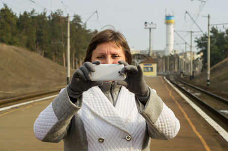 snapshot: A woman takes a snapshot by mobile phone while standing on a rail station