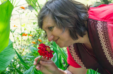 coral colored: A woman in a coral colored dress sniffing a red rose Stock Photo