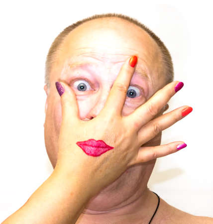 whose: Funny portrait of a man whose face covers a womans hand with painted lipstick mouth and whose nails covered with nail polish of different colors on white background cloth Stock Photo