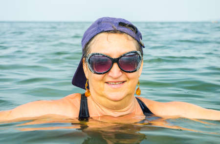 Woman in sunglasses and a baseball cap sits in the sea poking his head