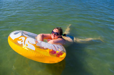 Woman in sunglasses on the inflatable buoy swimming in a sea Stock Photo