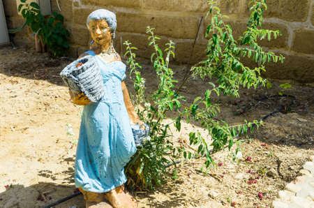 JERICHO, ISRAEL - MAY 2: The statue of a girl with a basket at the entrance to the monastery Gerasim Jordan May 2, 2016 in the Judean desert near Jericho, Israel Stock Photo