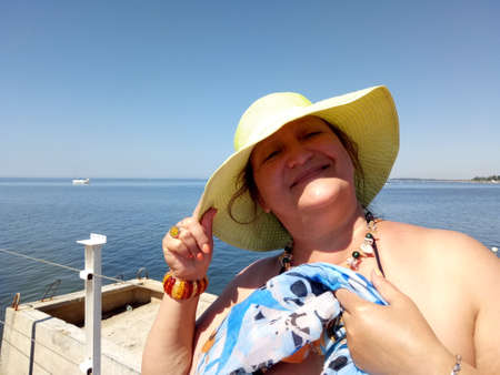 sunburnt: Portrait of a sunburnt woman standing on a pier holding a hat in the wind
