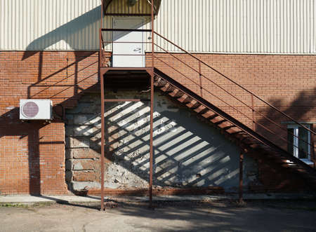 Brick wall with destruction, with iron staircase to the second floor. City background. Photo