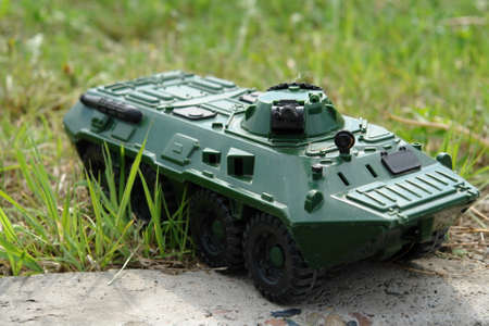 Photo a green toy tank on grass. Theme of meeting, coup or rebellion. Photo