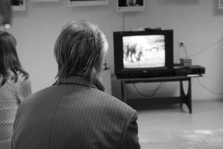 Elderly gray-haired man in jacket watching TV in hall of provincial museum. View from the back. Photo Banque d'images