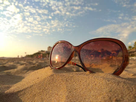 Sunglasses in the sand on shore. Concept: tourism, beach vacation, travel. Reflection of the setting sun
