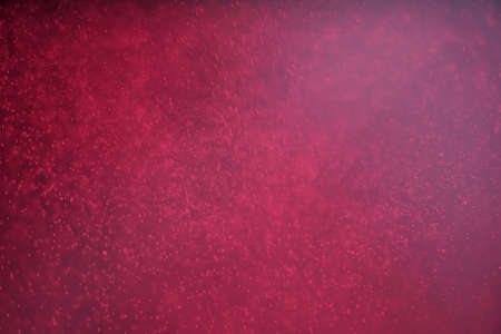 Abstract festive background with selective focus. Bright particles on dark red background. Splashes, space, energy flow with defocused bokeh 免版税图像