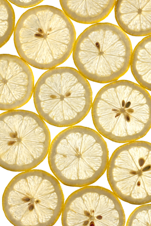 thinly sliced lemons on a white background in studio photo