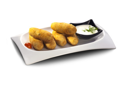 Delicious potato croquettes with sauce decorated with herbs isolated on white plate photo