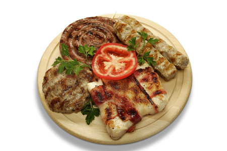 mixed grill of pork on a wooden mat photo