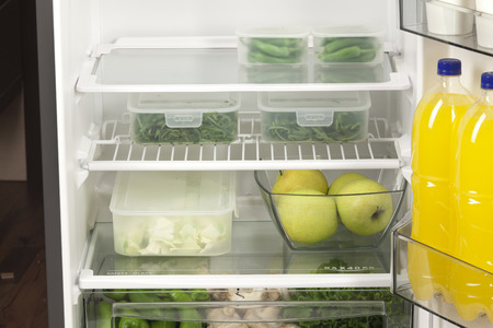 Fruits and vegetables in two containers in a modern fridge - a healthy food concept.