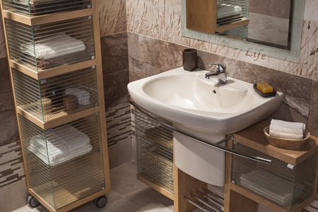 hotel bathroom: detail of a modern bathroom with sink and cupboard for towels Stock Photo