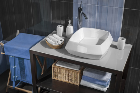 bathroom: detail of a modern bathroom with sink and accessories bathroom cabinet and blue bathroom tiles