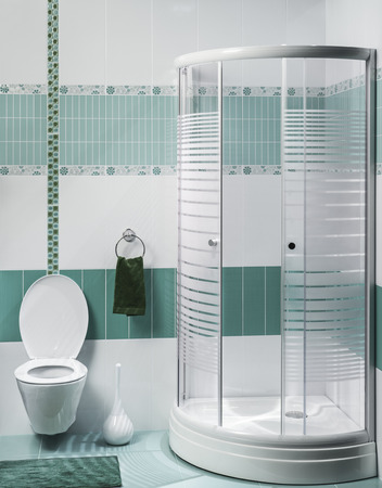 detail of a modern bathroom interior with luxury shower, green and white tiles
