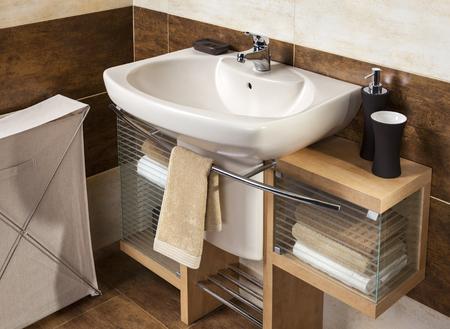シンクやアクセサリー、バスルーム キャビネットと茶色の浴室のタイルのモダンなバスルームの詳細