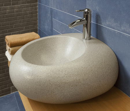 vessel sink: detail of a modern bathroom with granite sink