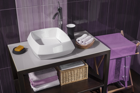 detail of a modern bathroom with sink and accessories, bathroom cabinet and purple bathroom tiles Reklamní fotografie