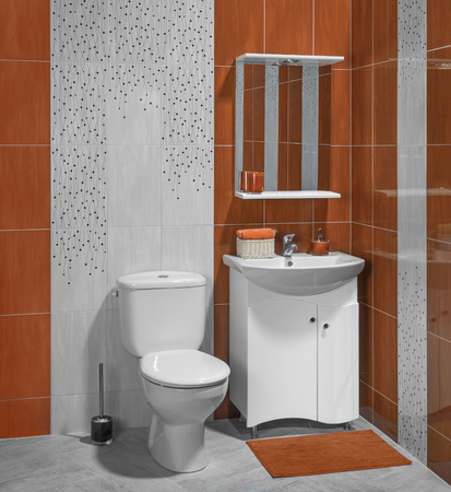 bathroom interior: Beautiful interior of bathroom with sink and toilet; decorated with orange tiles