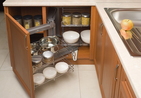 kitchen furniture: detail of open kitchen cabinet with cans of beans Stock Photo