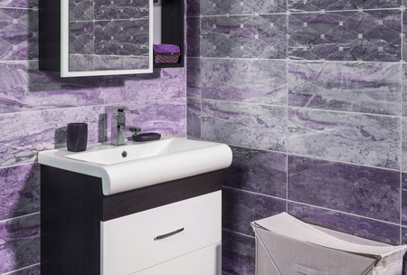 en suite: detail of fashionable bathroom in purple and gray color - toilet and sink