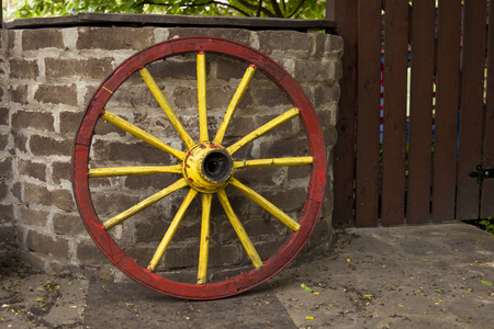 old wagon wheel with metal rim leaning on a stone wall Stock Photo