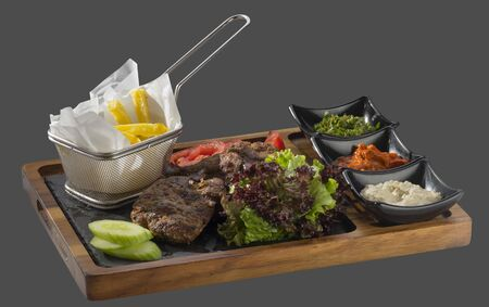 overflows: meatballs minced pork and veal garnished with fried potatoes with three kinds of sauce served in a bowl made of wood and stone