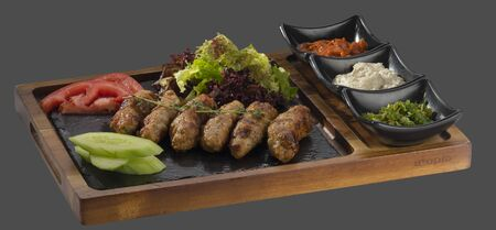 overflows: meatballs minced pork and veal garnished with green salad with three kinds of sauce served in a bowl made of wood and stone Stock Photo