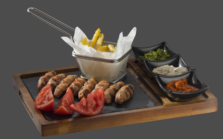 minced meat grilled with a side of fries with three kinds of sauce served in a bowl made of wood and stone