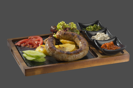 overflows: sausage of minced meat on the grill garnish of fried potatoes with three kinds of sauce served in a bowl made of wood and stone Stock Photo