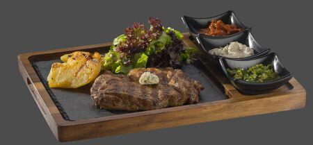 焼きたてのジャガイモと木と石で 3 種類の sosservirano 裁判所のグリーン サラダ添え豚のステーキ
