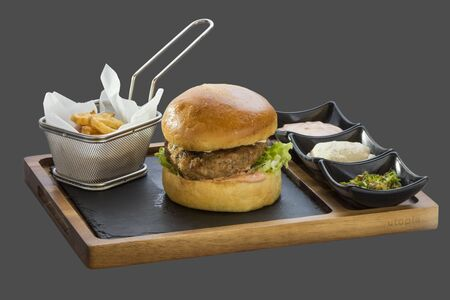 overflows: burger patty and garnish with fried potatoes and three kinds of sauce served in a bowl made of wood and stone Stock Photo