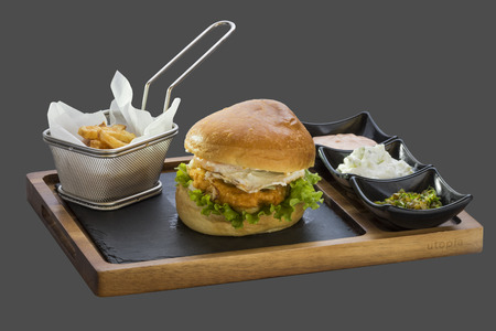 overflows: Burger with fried meat, garnish fried potatoes and three kinds of sauce served in a bowl made of wood and stone Stock Photo