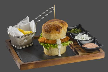 overflows: Burger with meat, lettuce and garnish with fried potatoes with three kinds of sauce served in a bowl made of wood and stone