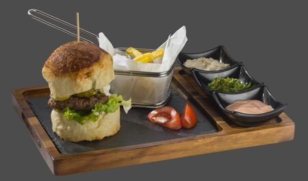 overflows: Burger with meat, pickles and a side of fries with three kinds of sauce served in a bowl made of wood and stone Stock Photo
