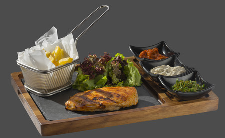 overflows: Chicken roasted with a side of fries with three kinds of sauce served in a bowl made of wood and stone