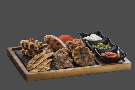 overflows: grilled different meats with three kinds of sauce served in a bowl made of wood and stone Stock Photo