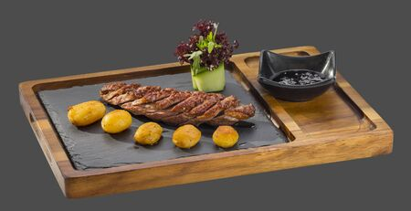 overflows: grilled meat with a side dish of potatoes and spicy sauce served in a bowl made of wood and stone