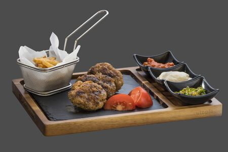 overflows: grilled minced meat balls with three kinds of sauce served in a bowl made of wood and stone Stock Photo