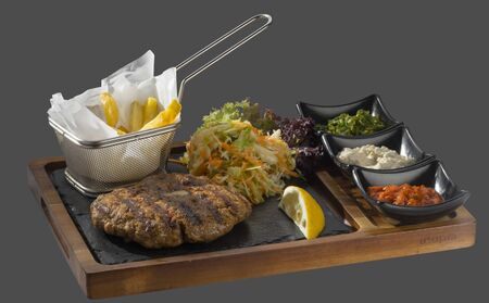 overflows: meatball from pmyano meat garnished with cabbage and fried potatoes with three kinds of sauce with three types sosservirano court in wood and stone Stock Photo