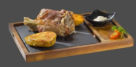 overflows: roasted pork knuckle with garnish of roasted and seasoned potatoes served in a bowl made of wood and stone