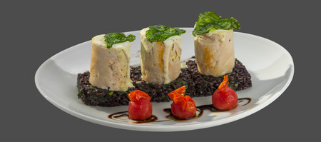 overflows: Roll meat with sauce on a bed of brown rice served in a bowl isolated on a gray background; Stock Photo