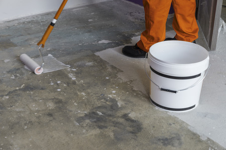 Worker puts primer with roller on concrete floor. House under construction Stok Fotoğraf