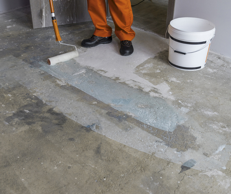 Renovation of partment. Worker puts primer with roller on concrete floor